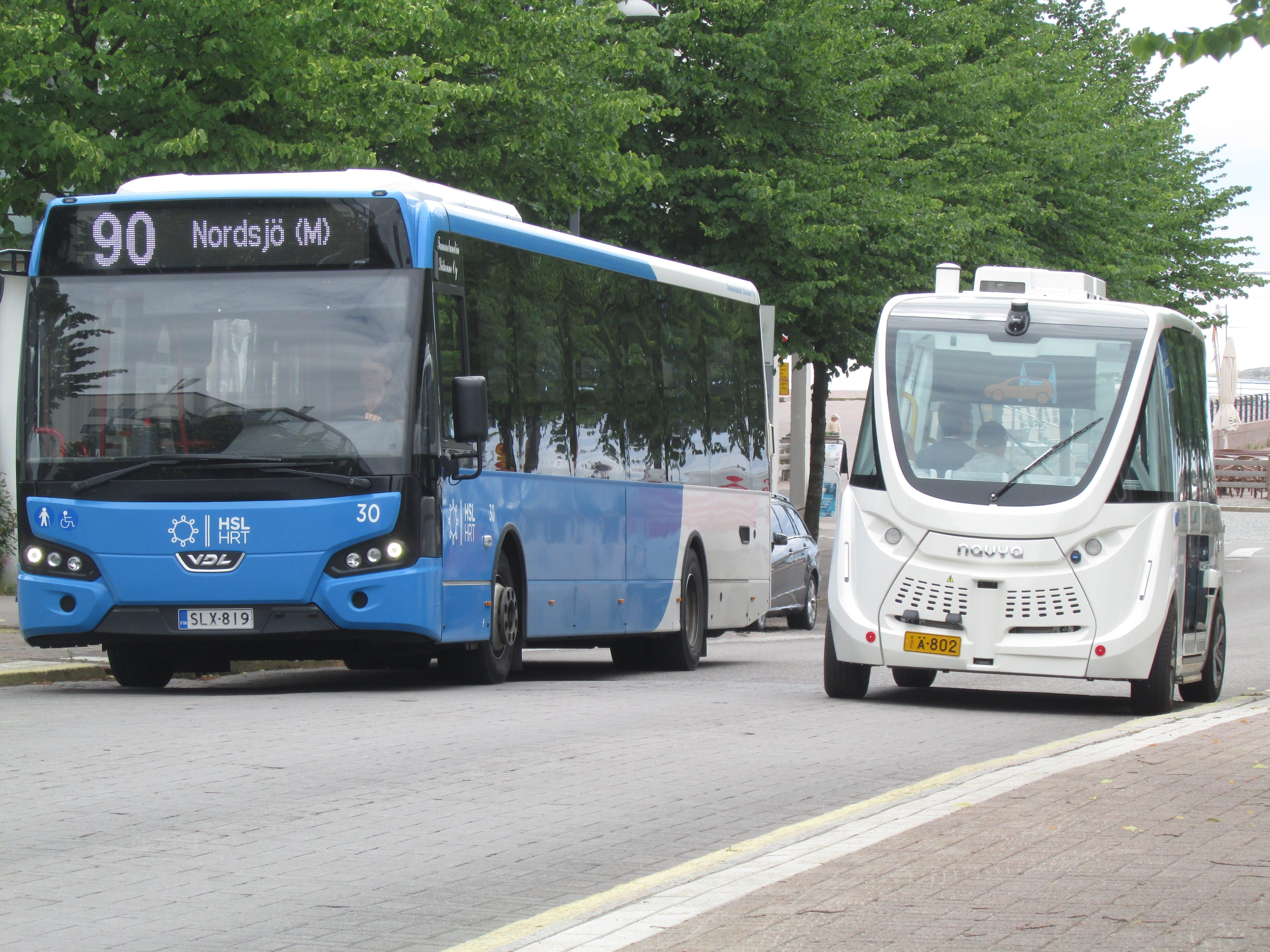 Perinteinen bussi ja vierellä moderni tietokoneohjattu minibussi.