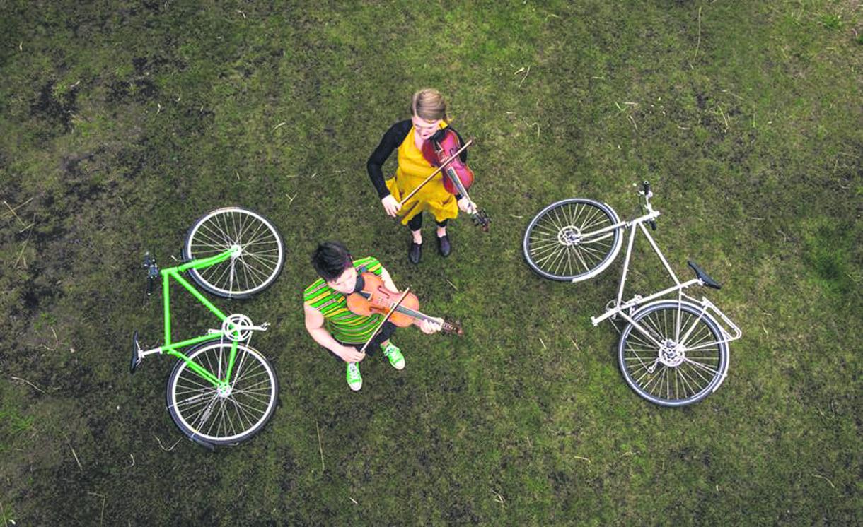 Viuluduo taittaa matkaansa polkypyörillä.