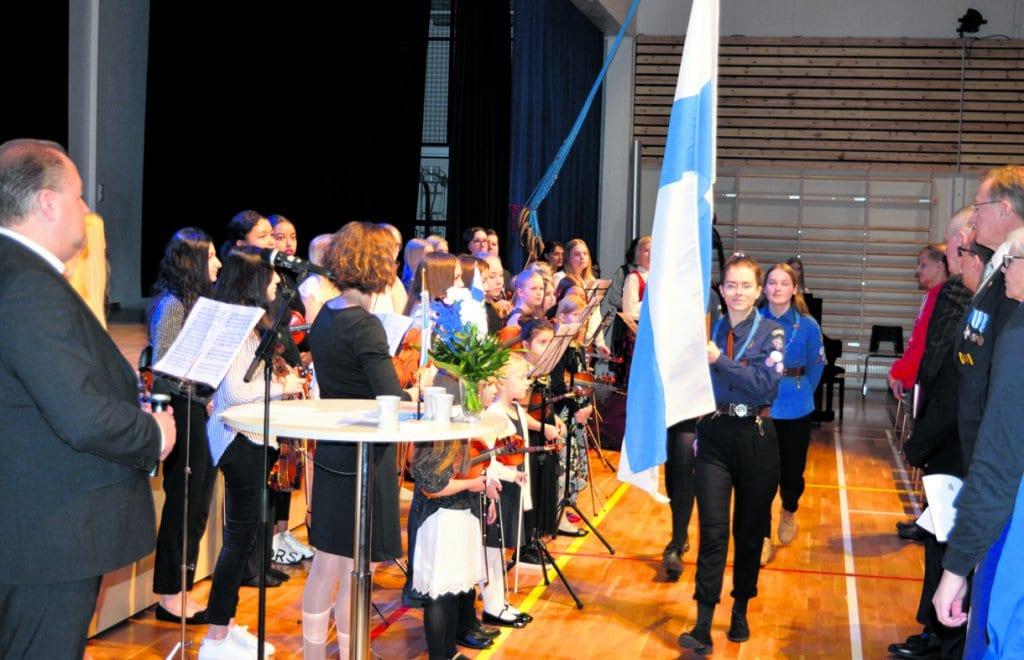 Kuvassa Vuosaaren Vesipääskyjen partiolaiset saattavat Suomen lipun saliin yleisön ja Vuosaaren musiikkikoulun jousiorkesterin todistaessa tapahtumaa.