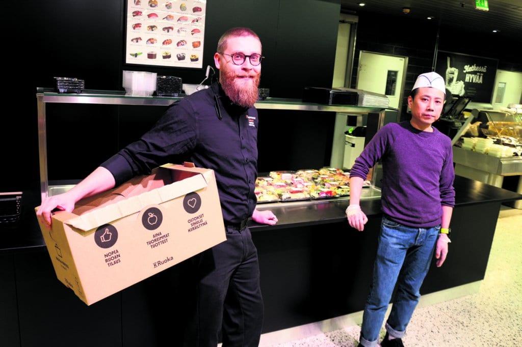 K-Supermarket Vuosaaren kauppias Sasu Hamina verkkokaupan tuotelaatikko kädessään.Vieressä Konnichiwan sushikokki Lyu Jian.