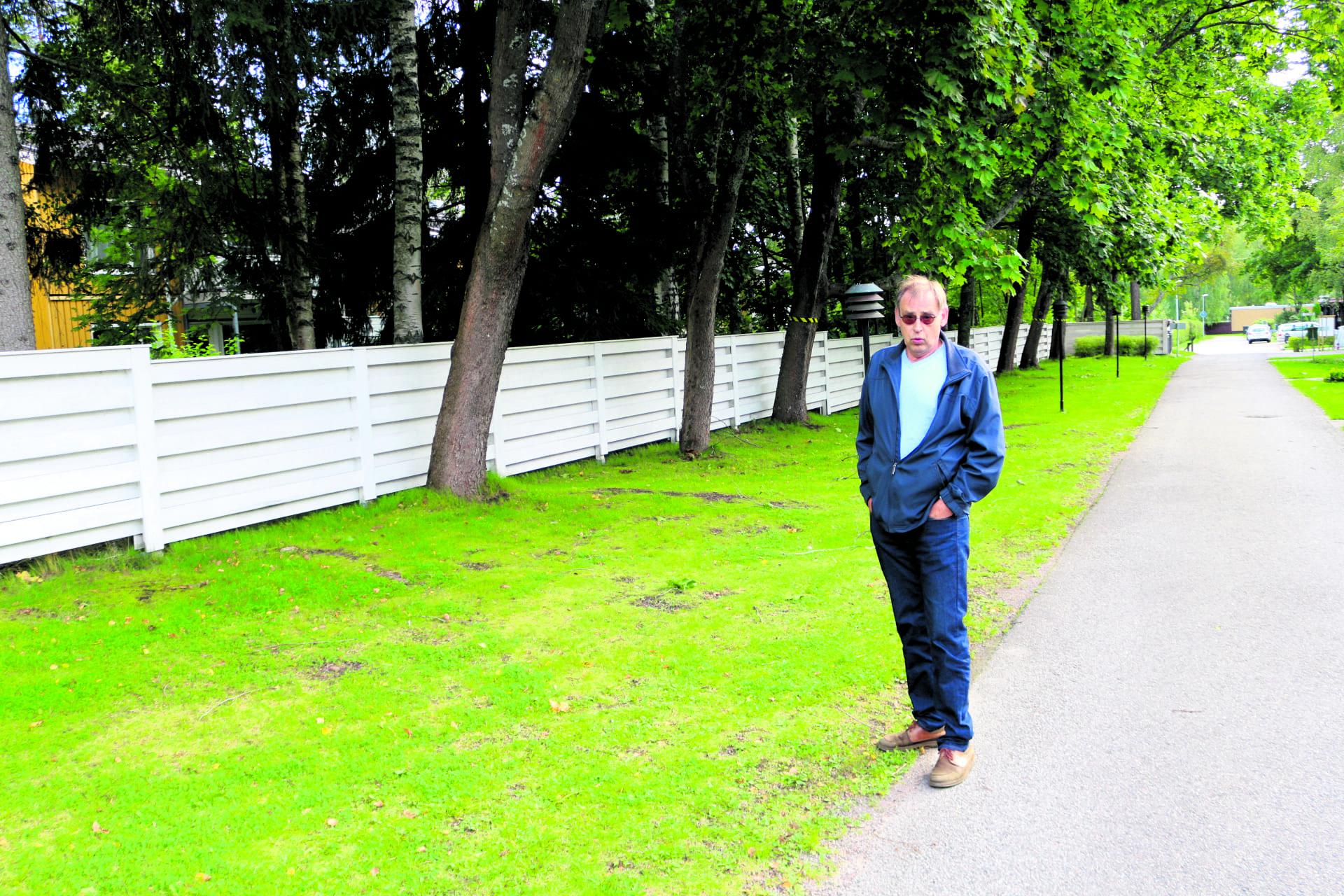 Jan-Olof Sillman seisoo Airoparintie 5–7:n tontilla kohdassa, jossa pommisuojana käytetty perunakellari sijaitsi sodan aikaan. Selän takana sijaitsevat Airoparintie ja Lokipolku. Kuva: Antti Honkanen