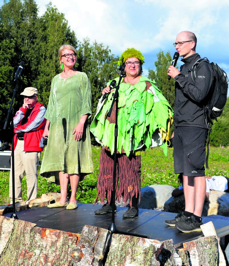 Puhujakorokkeella Rakkauden Metsä -idean äiti Anu Nylund, tilaisuuden juontanut Täti Vihreä ja ideaa eteenpäin vienyt Leo Stranius. Taustalla vuoroaan odottaa juhlapuhuja Markku Kulmala.