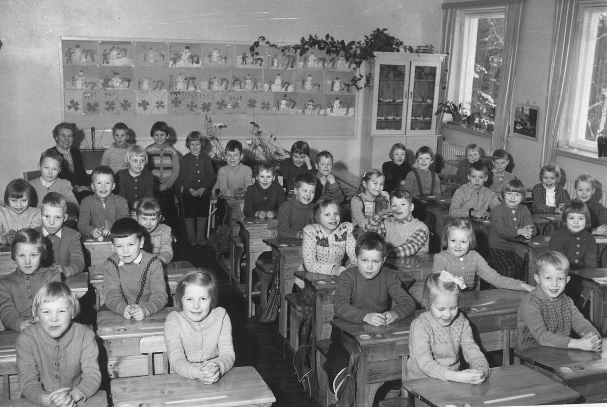 Seija Mäkisen sisko Eila Mäkinen ensimmäisen luokan luokkakuvassa vuonna 1958 Heteniityntiellä sijainneen Rannikkopiirin kansakoulussa. Eila istuu edestä katottuna toisena oikealla, ikkunan alla, patterin vieressä. Vuonna 1950 valmistunutta Rannikkopiirin kansakoulua kutsuttiin aluksi Sasekan kouluksi, sillä Vuosaaren ensimmäinen suomenkielinen koulu rakennettiin Sasekan aloitteesta yhtiön lahjoittamalle tontille. 1960-luvun alussa nimi muuttui Vuosaaren kansakouluksi, sittemmin Heteniityn ala-asteeksi, nykyään koulu on osa Vuoniityn peruskoulua. Kuva: Seija Mäkisen kotialbumi