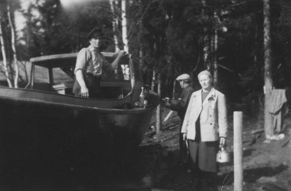 Ensio Mäkinen kunnostamassa venettään. Kuvassa myös vuosaarelainen kalastajapariskunta Axel ja Rosa (kahvipannu kädessään) Forström.