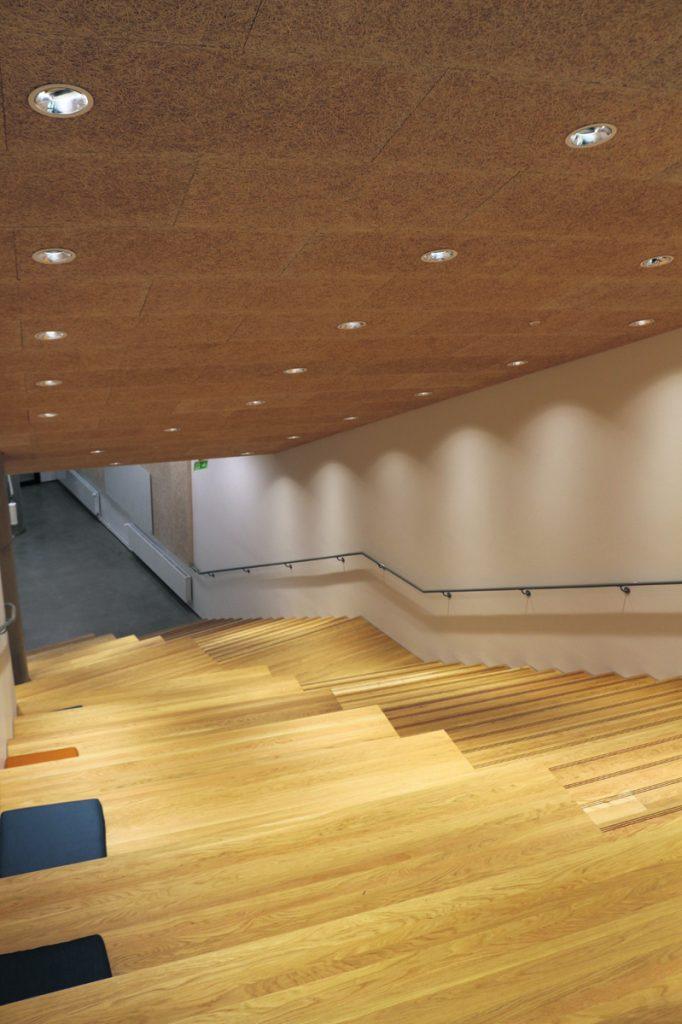 Upea puinen portaikko johtaa alimpaan kerrokseen, josta löytyy myös asukkaiden käyttöön tarkoitettu kaupunkiverstas. Tilat aukeavat tammikuussa 2022.