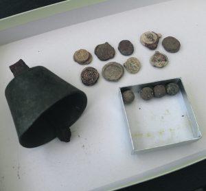 Kuvassa on Skatan tilan ympäristöstä metallinpaljastimella löytynyt vanha soittokello, sinettejä sekä musketin kuulia.