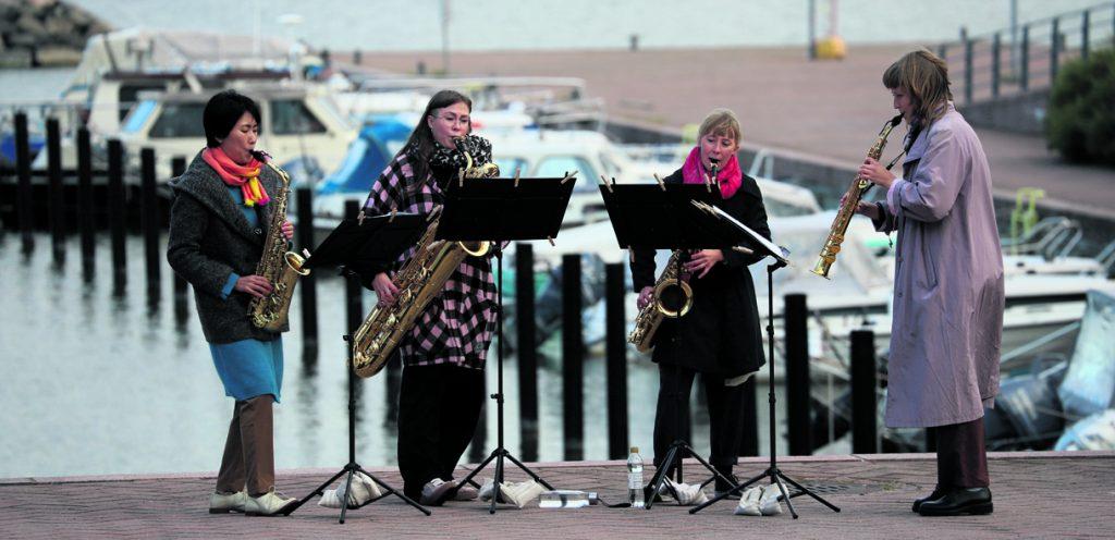Asukkaiden riemuksi Hiekkalaiturin aukiolla saatiin kuulla upea konsertti lauantaina 4.9. kello 18. Kyseessä oli korttelikonsertti, joita järjestettiin asukkaiden toivomuksesta ympäri kaupunkia Helsingin juhlaviikkoihin liittyen. Nykymusiikkia ja klassista soittanut saksofonikvartetti Saxotronauts, eli Anna-Sofia Anttonen, sopraanosaksofoni, Nanako Lammi, alttosaksofoni, Sikri Lehko, tenorisaksofoni ja Nanna Ikonen, baritonisaksofoni, toivat iloa asukkaiden iltapäivään. Kuva: Pekka Korpimies